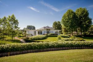 exclusieve tuin voorzien van bloemrijke borders met grote bloeiende stuiken voorzien van witte bloemen voor een tijdloze klassieke tuin en borders omgeven door een groot gazon