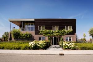 strakke tuin voorzien van bloemrijke borders voor een luchtig tuinontwerp wat voor een exclusieve tuin sfeer zorgt bij aankomst aan de voorzijde van de woning
