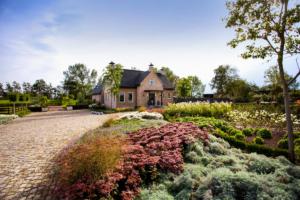 grote voortuin voorzien van borders met vaste planten die een landschapstuin vormen aan de voorzijde van deze vrijstaande woning
