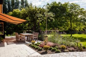 ruim terras voorzien van sierbestrating aansluitend borders die voorzien zijn van vaste struiken en planten
