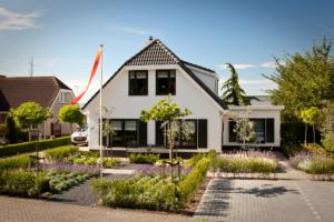 symmetrische borders als voortuin bij deze vrijstaande woning met vaste struiken en planten in de strak vormgegeven borders