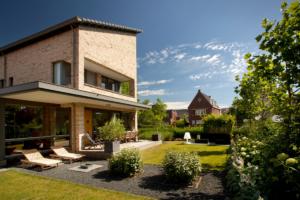 strak ontworpen tuin voorzien van moderne materialen zoals donker grind en strakke vormen in de borders
