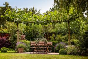 zithoek gerealiseerd in een landschapstuin omgeven door vaste struiken met eenjarige bloeiende planten in terrasmanden