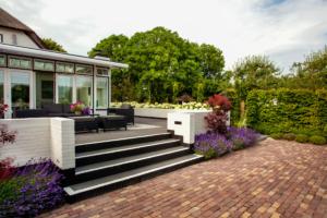 sierbestrating bij zithoek en terras voor deze woning met zomer bloeiende struiken welke sfeer en kleur meegeven aan de tuin