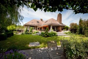 klassiek aangelegde tuin bij vrijstaande villa welke zorgen voor een exclusieve tuin en onderstreping van deze woning zodat binnen en buiten een geheel vormen