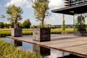 Duurzaam houten terras omgeven door waterpartij en siergras zodat er een mooi terras ontstaat in strakke lijnen welke dit moderne nieuwbouw bedrijfspand ondersteunen in het geheel te Oudewater