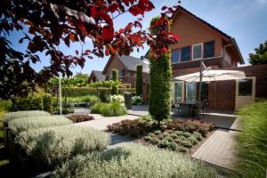 borders voorzien van vaste planten en struiken geven deze tuin een strak uiterlijk zonder karakter te verliezen door de manier van tuinontwerp is toegepast met strakke lijnen en symmetrisch ontworpen borders met vaste planten in Oudewater