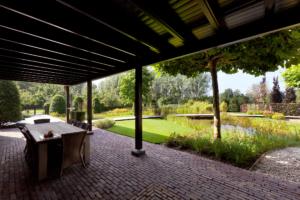 veranda aan de woning gevestigd om te genieten van een overdekt terras in de landschapstuin voorzien van een vijver welke zorgt voor een speelse waterpartij voorzien van borders met vaste struiken en planten omringt door strak vormgegeven gazon in Oudewater en Benschop