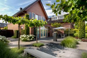 Terras en zithoek vormen een geheel tegen de achtergevel van de woning de bomen zorgen voor beschutting en de vaste bloeiende planten voor sfeer