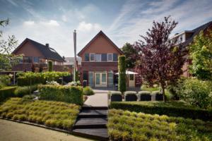 strak tuinontwerp voor een onderhoudsvriendelijke tuin voorzien van terraspotten met siergras, winterharde struiken en vaste planten gelegen aan de waterkant aan de achterzijde van deze vrijstaande woning in Oudewater en Linschoten