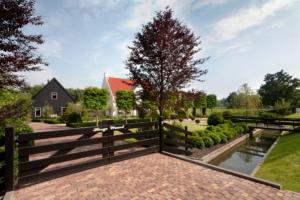 bestrating bij de oprit van de landschapstuin welke gescheiden wordt door een tuinhek van hoogwaardig tuinhout
