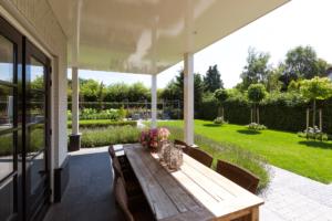Groot terras voorzien van een grote tuintafel welke zorgt voor een sfeervolle zithoek welke gebruikt kan worden in veel jaargetijden zeker door de overkapping van de veranda welke opgenomen zijn in het tuinontwerp en tuinaanleg in Benschop en Bodegraven