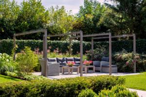 tuinontwerp in combinatie met een strak terras wat het karakter van een strakke tuin benadrukt. Door gebruik te maken van tuinhout bij de zithoek geeft het toch een natuurlijke uitstraling zonder dat het ten koste gaat van het exclusieve gevoel. Het terras is omgeven met bloemrijke borders voorzien van een grote kleurenpracht